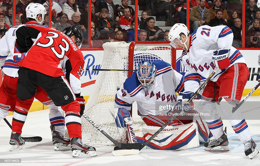 <a gi-track='captionPersonalityLinkClicked' href=/galleries/search?phrase=Henrik+Lundqvist&family=editorial&specificpeople=217958 ng-click='$event.stopPropagation()'>Henrik Lundqvist</a> of the New York Rangers makes a save as team mate <a gi-track='captionPersonalityLinkClicked' href=/galleries/search?phrase=Derek+Stepan&family=editorial&specificpeople=4687181 ng-click='$event.stopPropagation()'>Derek Stepan</a> #21 defends against Jakob Silfverberg #33 of the Ottawa Senators, during an NHL game at Scotiabank Place on February 21, 2013 in Ottawa, Ontario, Canada.