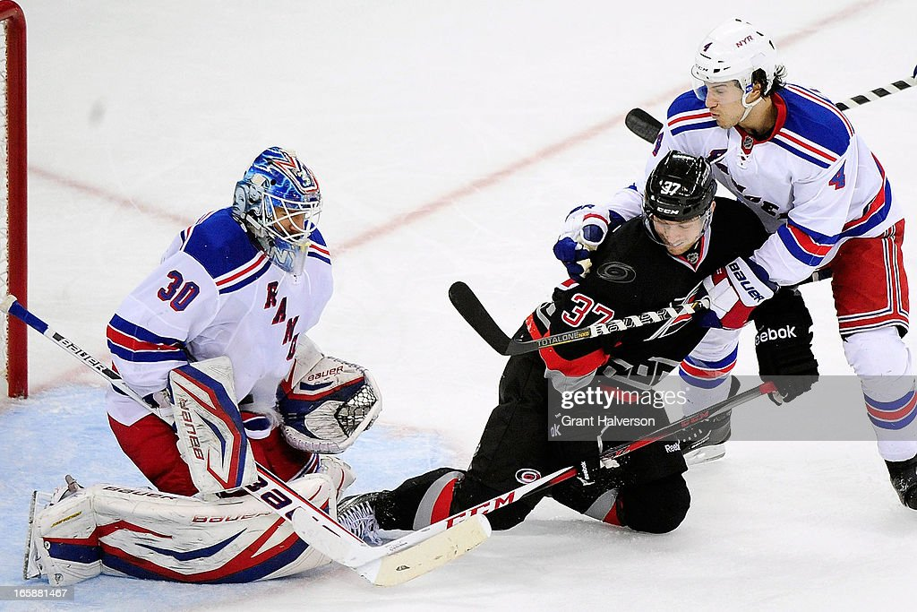 <a gi-track='captionPersonalityLinkClicked' href=/galleries/search?phrase=Henrik+Lundqvist&family=editorial&specificpeople=217958 ng-click='$event.stopPropagation()'>Henrik Lundqvist</a> #30 of the New York Rangers makes a save as teammate <a gi-track='captionPersonalityLinkClicked' href=/galleries/search?phrase=Michael+Del+Zotto&family=editorial&specificpeople=4044191 ng-click='$event.stopPropagation()'>Michael Del Zotto</a> #4 defends <a gi-track='captionPersonalityLinkClicked' href=/galleries/search?phrase=Tim+Brent&family=editorial&specificpeople=2190959 ng-click='$event.stopPropagation()'>Tim Brent</a> #37 of the Carolina Hurricanes during play at PNC Arena on April 6, 2013 in Raleigh, North Carolina. The Rangers won 4-1.