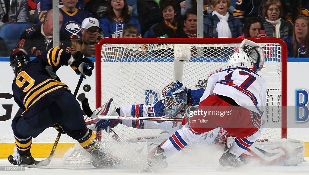 Henrik Lundqvist #30 of the New York Rangers makes a save in front of teammate John Moore #17 and Steve Ott #9 of the Buffalo Sabres at First Niagara Center on April 19, 2013 in Buffalo, New York.
