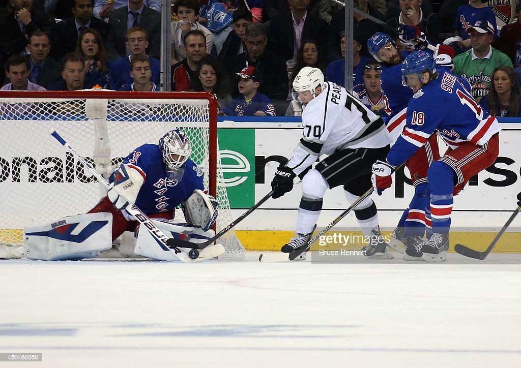Henrik Lundqvist #30 of the New York Rangers makes a save on Tanner Pearson #70 of the Los Angeles Kings with Marc Staal #18 of the New York Rangers defending during the second period of Game Four of the 2014 NHL Stanley Cup Final at Madison Square Garden on June 11, 2014 in New York, New York.