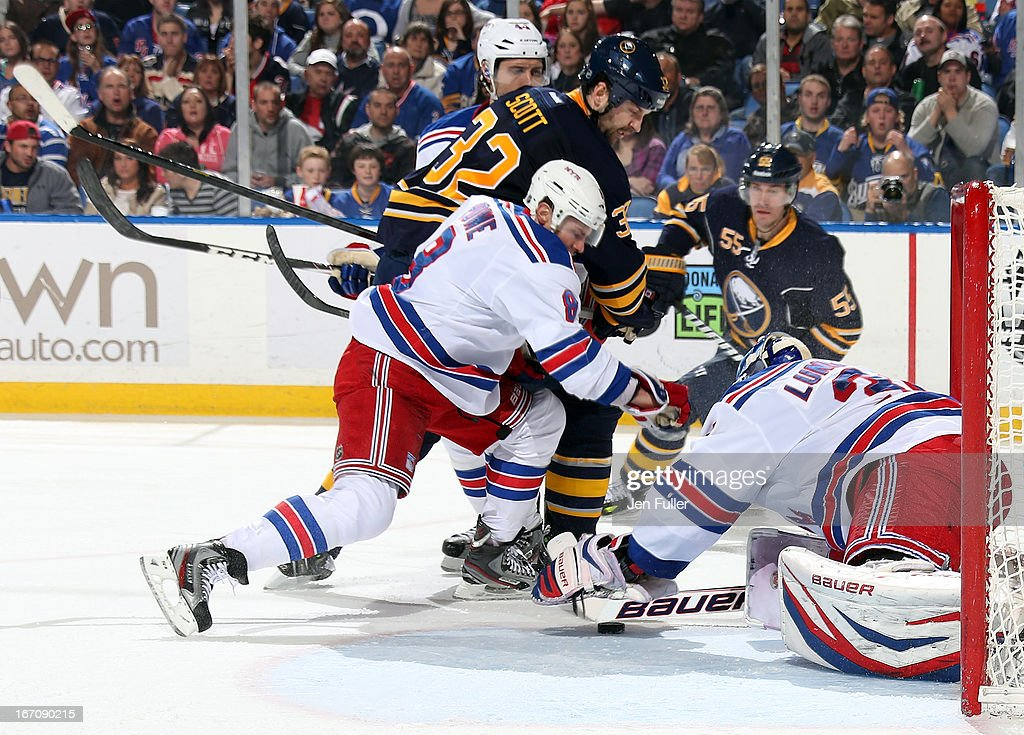 Henrik Lundqvist #30 of the New York Rangers makes a second-period save in front of teammate Darroll Powe #8 and John Scott #32 of the Buffalo Sabres at First Niagara Center on April 19, 2013 in Buffalo, New York.