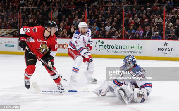 Henrik Lundqvist of the New York Rangers poke checks the puck away from Ryan Dzingel of the Ottawa Senators as Dan Girardi of the New York Rangers...
