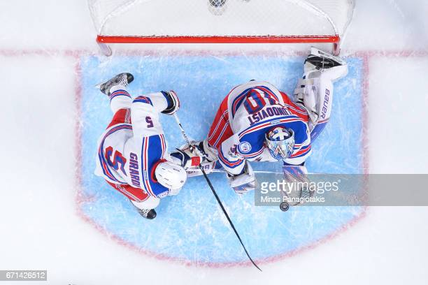 Henrik Lundqvist of the New York Rangers prepares to glove the puck near teammate Dan Girardi against the Montreal Canadiens in Game Five of the...