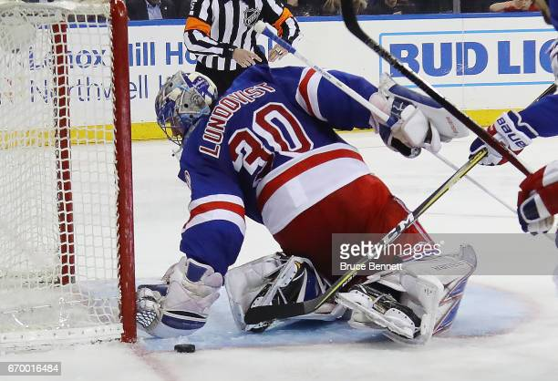 Henrik Lundqvist of the New York Rangers reaches behind himself to grab a shot by Alexander Radulov of the Montreal Canadiens during the third period...