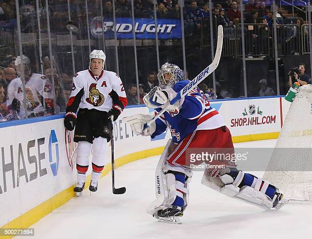 Henrik Lundqvist of the New York Rangers shoots the puck away from Chris Neil of the Ottawa Senators during the third period at Madison Square Garden...