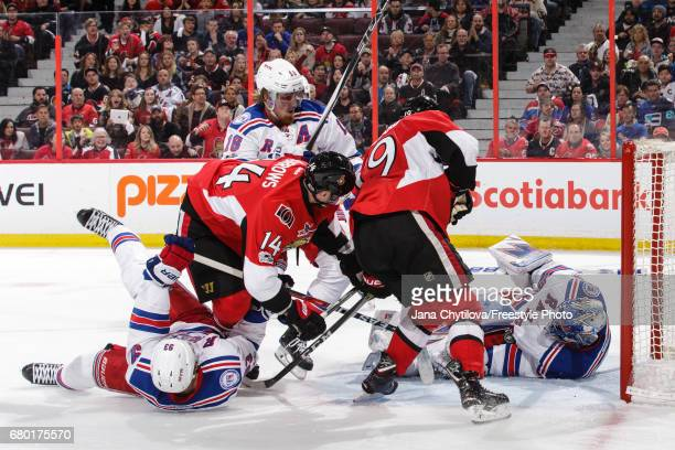 Henrik Lundqvist of the New York Rangers stops the puck between his pad and arm as Derick Brassard and Alexandre Burrows look for a rebound and Mika...
