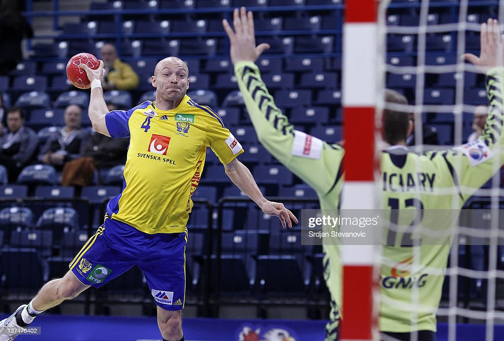 Henrik Lundstrom (L) of Sweden scores a goal past goalkeeper Marcin Wichary (R) of Poland during the Men's European Handball Championship 2012 main group 1 match between Poland and Sweden at Belgrade Arena Hall on January 21, 2011 in Belgrade, Serbia.