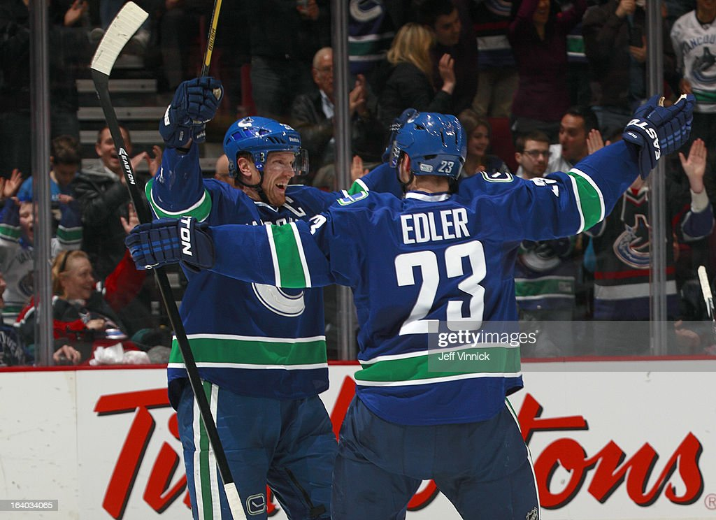 Henrik Sedin #33 and Alexander Edler #23 of the Vancouver Canucks celebrates a power-play goal against the Minnesota Wild during their NHL game at Rogers Arena March 18, 2013 in Vancouver, British Columbia, Canada.