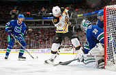Henrik Sedin and Christopher Tanev of the Vancouver Canucks watch as David Krejci of the Boston Bruins bangs at a loose puck at the feet of Ryan...
