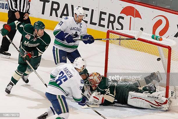 Henrik Sedin and the Vancouver Canucks narrowly miss a goal against Eric Nystrom Greg Zanon and goalie Anton Khudobin of the Minnesota Wild during...