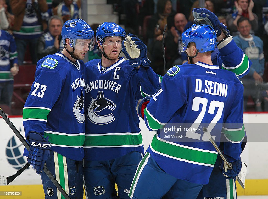 Henrik Sedin #33, Daniel Sedin #22 and Alexander Edler #23 of the Vancouver Canucks of the Vancouver Canucks celebrate a goal against the Anaheim Ducks during their season-opening NHL game at Rogers Arena January 19, 2013 in Vancouver, British Columbia, Canada. Anaheim won 7-3.