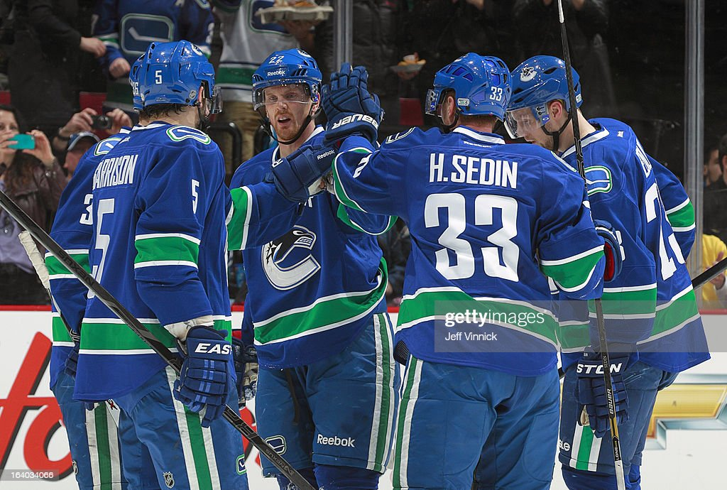 Henrik Sedin #33, Daniel Sedin #22 and Jason Garrison #5 of the Vancouver Canucks celebrate a power-play goal against the Minnesota Wild during their NHL game at Rogers Arena March 18, 2013 in Vancouver, British Columbia, Canada.