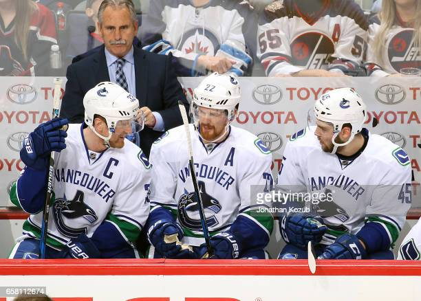 Henrik Sedin Daniel Sedin and Michael Chaput of the Vancouver Canucks discuss strategy on the bench during second period action against the Winnipeg...