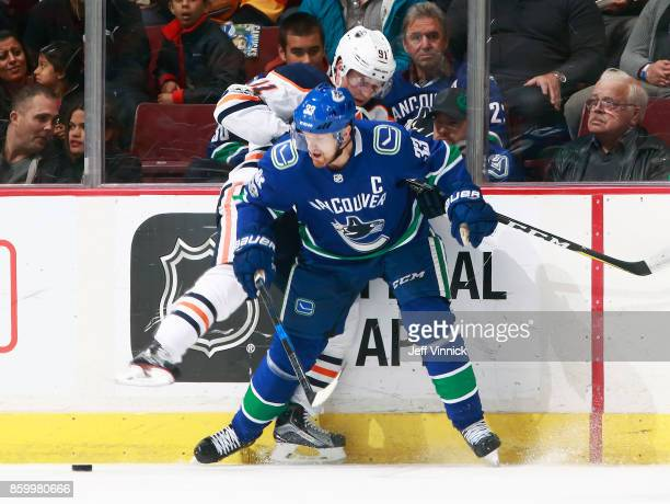 Henrik Sedin of the Vancouver Canucks and Drake Caggiula of the Edmonton Oilers battle for the puck along the boards during their NHL game at Rogers...