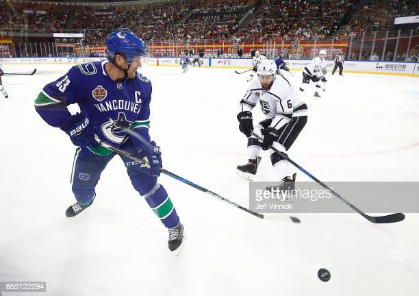 Henrik Sedin of the Vancouver Canucks and Jake Muzzin of the Los Angeles Kings watch a loose puck during their preseason game at Cadillac Arena...