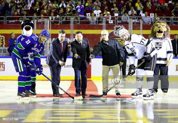 Henrik Sedin of the Vancouver Canucks and Jeff Carter of the Los Angeles Kings take a ceremonial faceoff from Dave Murphy Sun Xuecai and Frank...