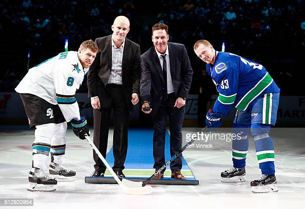Henrik Sedin of the Vancouver Canucks and Joe Pavelski of the San Jose Sharks take the ceremonial faceoff from former Canucks Sami Salo and Ed...
