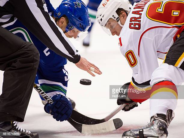 Henrik Sedin of the Vancouver Canucks and Markus Granlund of the Calgary Flames faceoff during NHL action on January 2015 at Rogers Arena in...