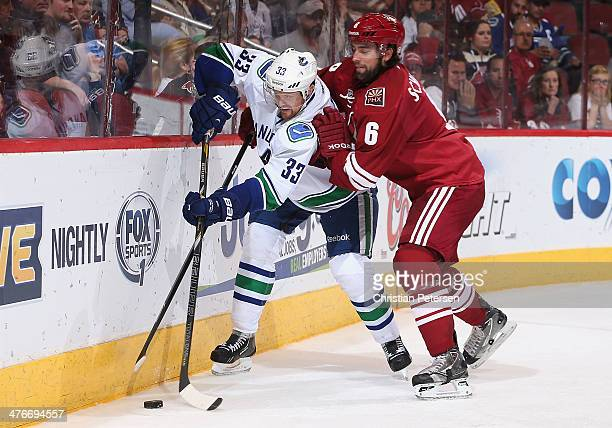 Henrik Sedin of the Vancouver Canucks attempts to control the puck under pressure from David Schlemko of the Phoenix Coyotes during the third period...