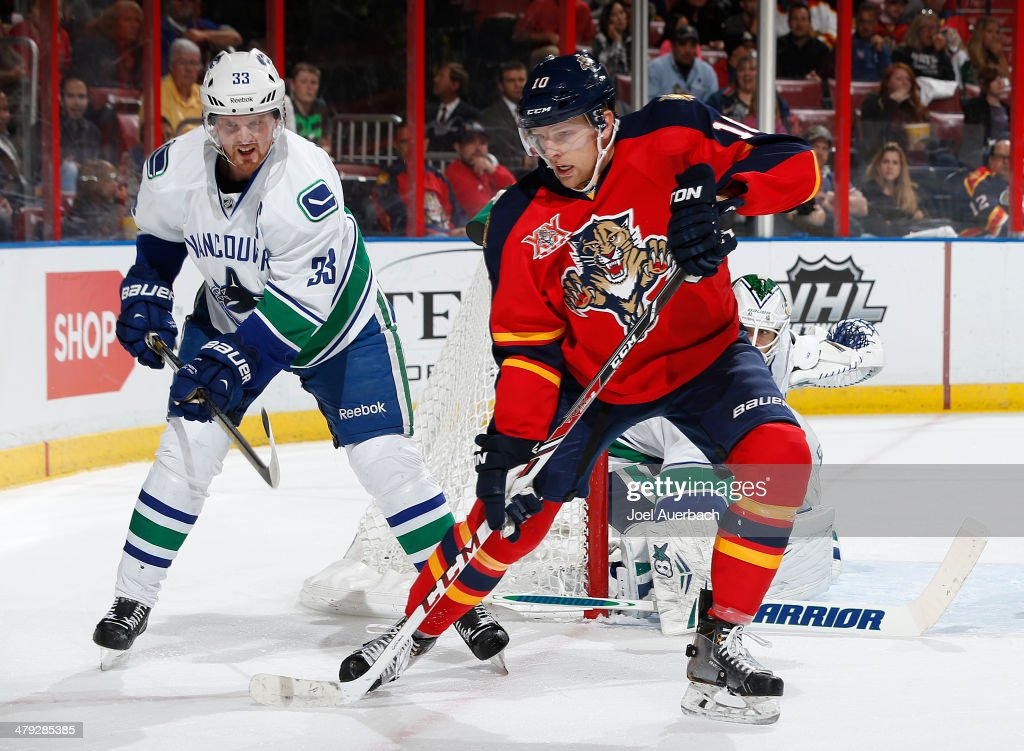 Henrik Sedin of the Vancouver Canucks attempts to take the puck from Joey Crabb of the Florida Panthers at the BBT Center on March 16 2014 in Sunrise...