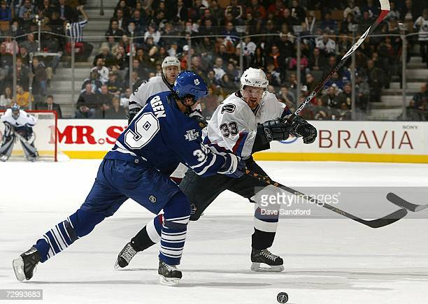 Henrik Sedin of the Vancouver Canucks battles for the puck as he is checked by Travis Green of the Toronto Maple Leafs during their NHL game at the...