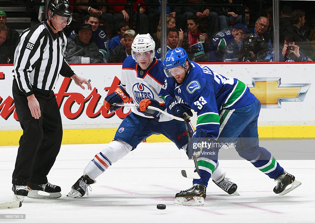 <a gi-track='captionPersonalityLinkClicked' href=/galleries/search?phrase=Henrik+Sedin&family=editorial&specificpeople=202574 ng-click='$event.stopPropagation()'>Henrik Sedin</a> #33 of the Vancouver Canucks beats <a gi-track='captionPersonalityLinkClicked' href=/galleries/search?phrase=Ryan+Nugent-Hopkins&family=editorial&specificpeople=7144190 ng-click='$event.stopPropagation()'>Ryan Nugent-Hopkins</a> #93 of the Edmonton Oilers to the puck during their NHL game at Rogers Arena April 4, 2013 in Vancouver, British Columbia, Canada. Vancouver won 4-0.