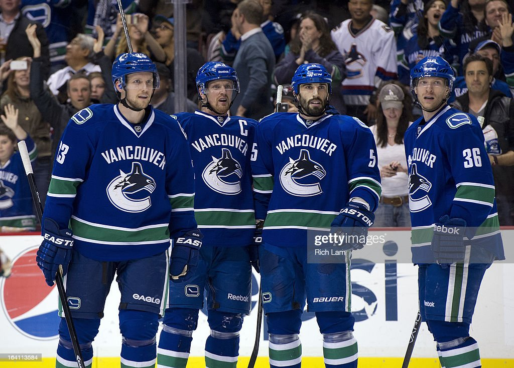 Henrik Sedin #33 of the Vancouver Canucks celebrates with teammates Alexander Edler #23, Jason Garrison #5 and Jannik Hansen 336 after scoring a goal during NHL action against the Minnesota Wild on March 18, 2013 at Rogers Arena in Vancouver, British Columbia, Canada.