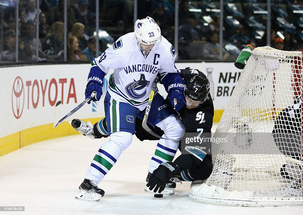 Henrik Sedin #33 of the Vancouver Canucks checks Paul Martin #7 of the San Jose Sharks as they go for the puck at SAP Center on March 31, 2016 in San Jose, California.