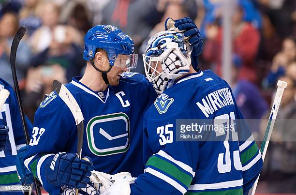 Henrik Sedin of the Vancouver Canucks congratulates goalie Jacob Markstrom after defeating the Calgary Flames 51 in NHL action on April 13 2014 at...
