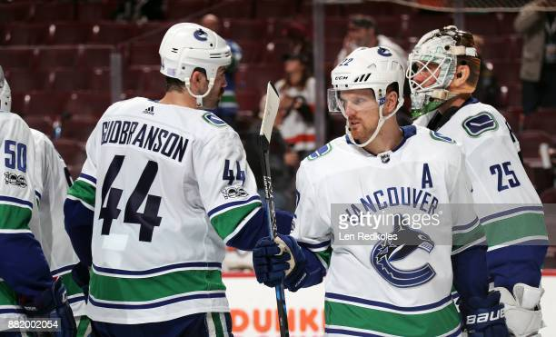 Henrik Sedin of the Vancouver Canucks congratulates teammates Jacob Markstrom and Erik Gudbranson after defeating the Philadelphia Flyers 52 on...