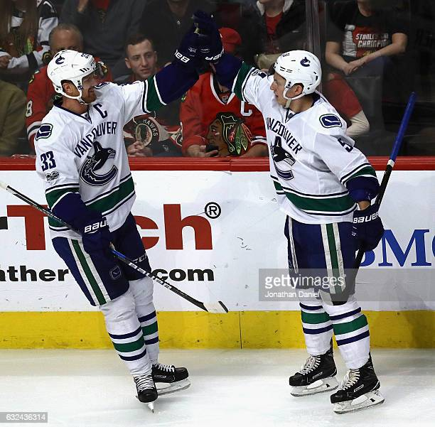 Henrik Sedin of the Vancouver Canucks congratulates Troy Stecher of the Vancouver Canucks after a third period goal against the Chicago Blackhawks at...