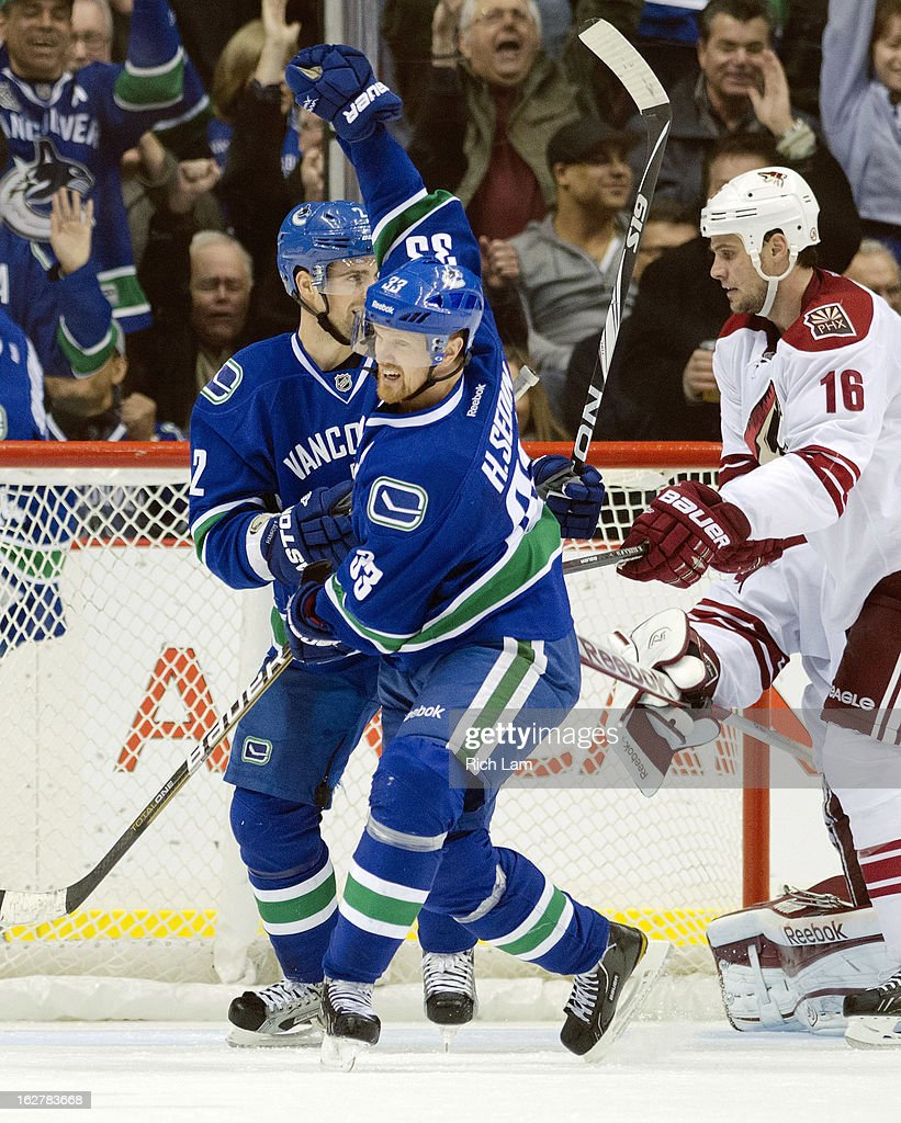 Henrik Sedin #33 of the Vancouver Canucks is congratulated by Dan Hamhuis #2 after scoring a goal as Rostislav Klesla #16 of the Phoenix Coyotes skates past during the third period in NHL action on February 26, 2013 at Rogers Arena in Vancouver, British Columbia, Canada.