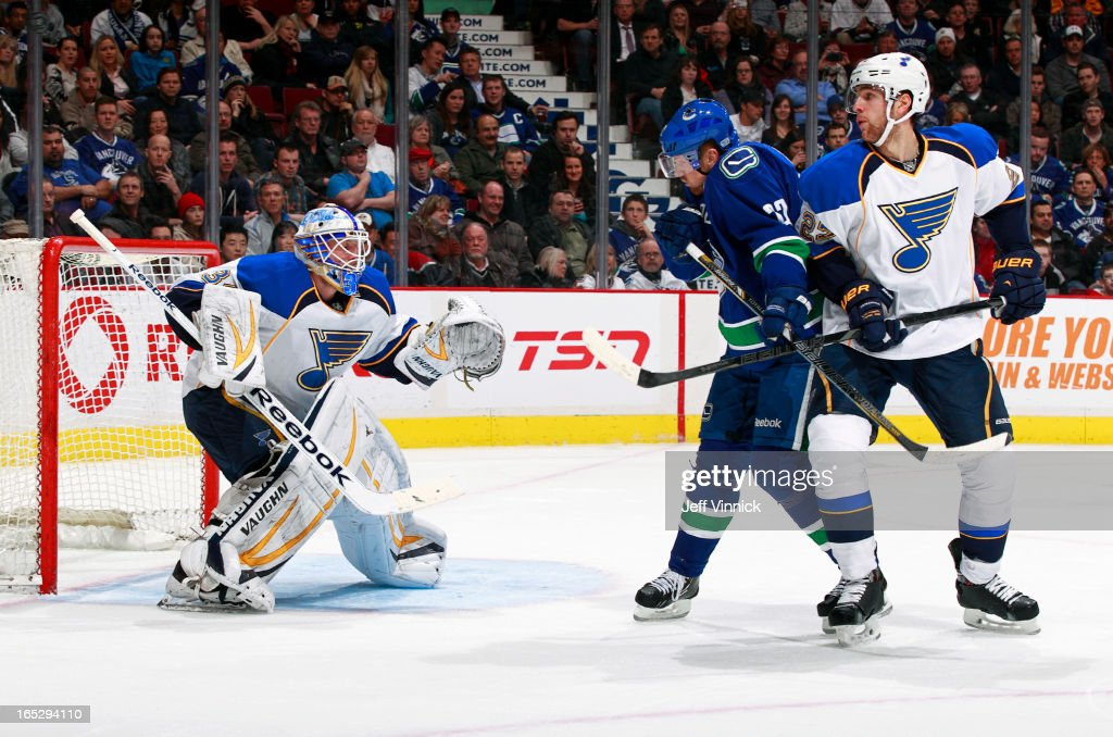 Henrik Sedin #33 of the Vancouver Canucks is tied up by Alex Pietrangelo #27 of the St. Louis Blues as Blues' goalie Jake Allen defends the net during an NHL game at Rogers Arena March 19, 2013 in Vancouver, British Columbia, Canada.