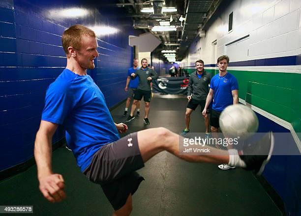 Henrik Sedin of the Vancouver Canucks kicks a soccer ball as he warms up with teammates before their NHL game against the Edmonton Oilers at Rogers...