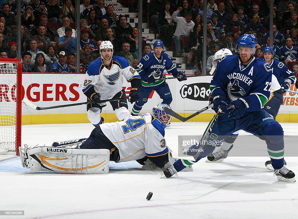 Henrik Sedin #33 of the Vancouver Canucks looks for the rebound on a save by goalie Jake Allen #34 of the St. Louis Blues during an NHL game at Rogers Arena March 19, 2013 in Vancouver, British Columbia, Canada.