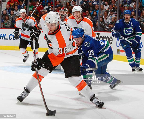 Henrik Sedin of the Vancouver Canucks looks on as Darroll Powe of the Philadelphia Flyers clears the puck from the zone during their game at Rogers...
