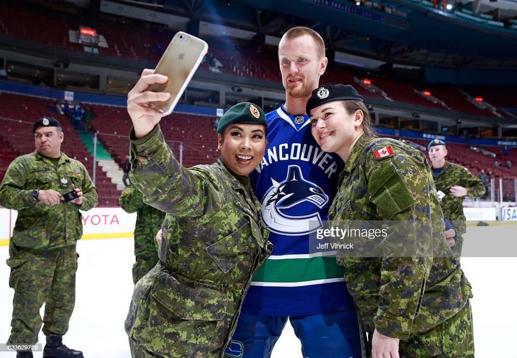 Henrik Sedin #33 of the Vancouver Canucks poses for a photo with Canadian military after their NHL game against the San Jose Sharks at Rogers Arena February 2, 2017 in Vancouver, British Columbia, Canada.