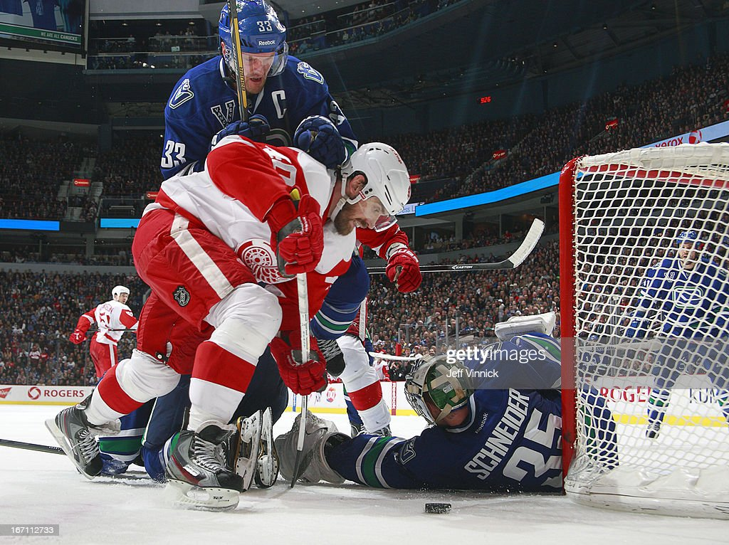 Henrik Sedin #33 of the Vancouver Canucks pushes Henrik Zetterberg #40 of the Detroit Red Wings after Cory Schneider #35 of the Canucks made a save during their NHL game at Rogers Arena April 20, 2013 in Vancouver, British Columbia, Canada. Vancouver won 2-1.