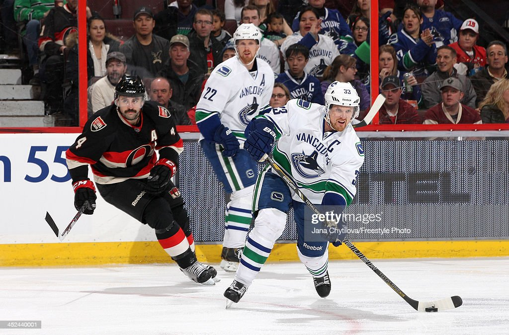 <a gi-track='captionPersonalityLinkClicked' href=/galleries/search?phrase=Henrik+Sedin&family=editorial&specificpeople=202574 ng-click='$event.stopPropagation()'>Henrik Sedin</a> #33 of the Vancouver Canucks shoots the puck as team <a gi-track='captionPersonalityLinkClicked' href=/galleries/search?phrase=Daniel+Sedin&family=editorial&specificpeople=202492 ng-click='$event.stopPropagation()'>Daniel Sedin</a> #22 and Chris Phillips #4 of the Ottawa Senators look on during an NHL game at Canadian Tire Centre on November 28, 2013 in Ottawa, Ontario, Canada.
