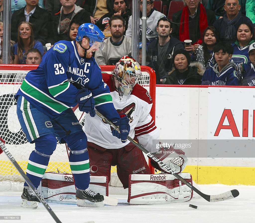 <a gi-track='captionPersonalityLinkClicked' href=/galleries/search?phrase=Henrik+Sedin&family=editorial&specificpeople=202574 ng-click='$event.stopPropagation()'>Henrik Sedin</a> #33 of the Vancouver Canucks tips the puck in front of Mike Smith #41 of the Phoenix Coyotes for a goal during their NHL game at Rogers Arena February 26, 2013 in Vancouver, British Columbia, Canada. Phoenix won 4-2.