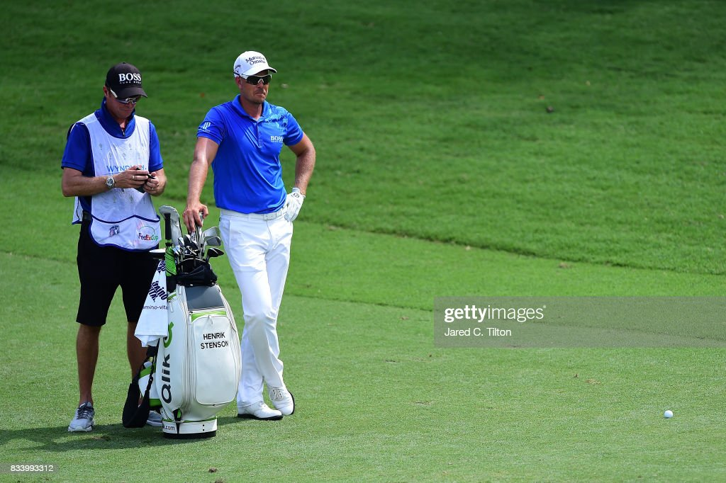 Henrik Stenson of Sweden and his caddie stand in the ninth fairway during the first round of the Wyndham Championship at Sedgefield Country Club on August 17, 2017 in Greensboro, North Carolina.