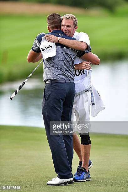 Henrik Stenson of Sweden celebrates his 3 shot victory with caddie Gareth Lord on the 18th green during the final round of the BMW International Open...