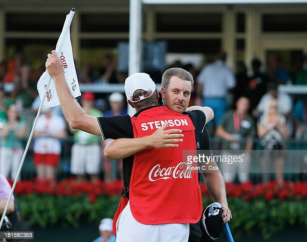Henrik Stenson of Sweden celebrates on the 18th green with his caddie Gareth Lord after winning the TOUR Championship by CocaCola and the FedExCup...