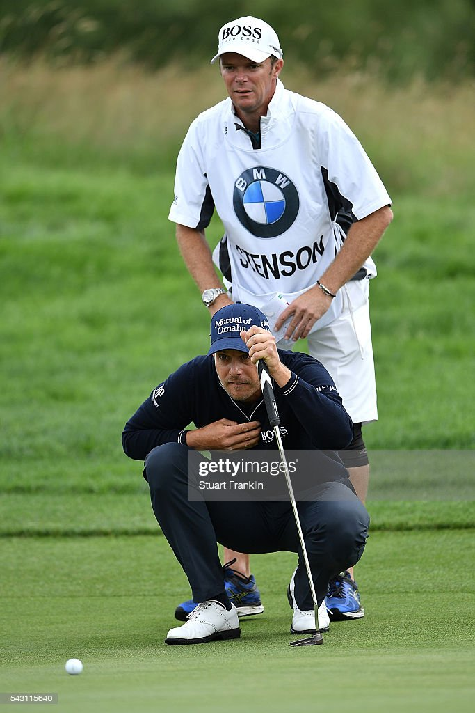 Henrik Stenson of Sweden lines up a putt with his caddie during the rain delayed third round of the BMW International Open at Gut Larchenhof on June 26, 2016 in Cologne, Germany.