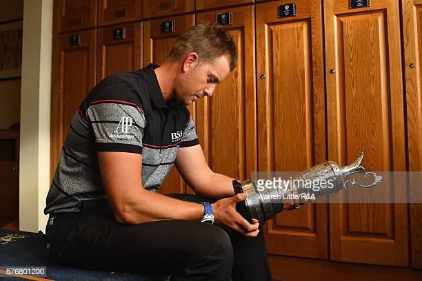 Henrik Stenson of Sweden looks at the Claret Jug in the Champions Locker Room following his victory during the final round on day four of the 145th...