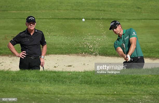 Henrik Stenson of Sweden plays a bunker shot as his coach Pete Cowen looks on during the Pro Am prior to the start of the Abu Dhabi HSBC Golf...