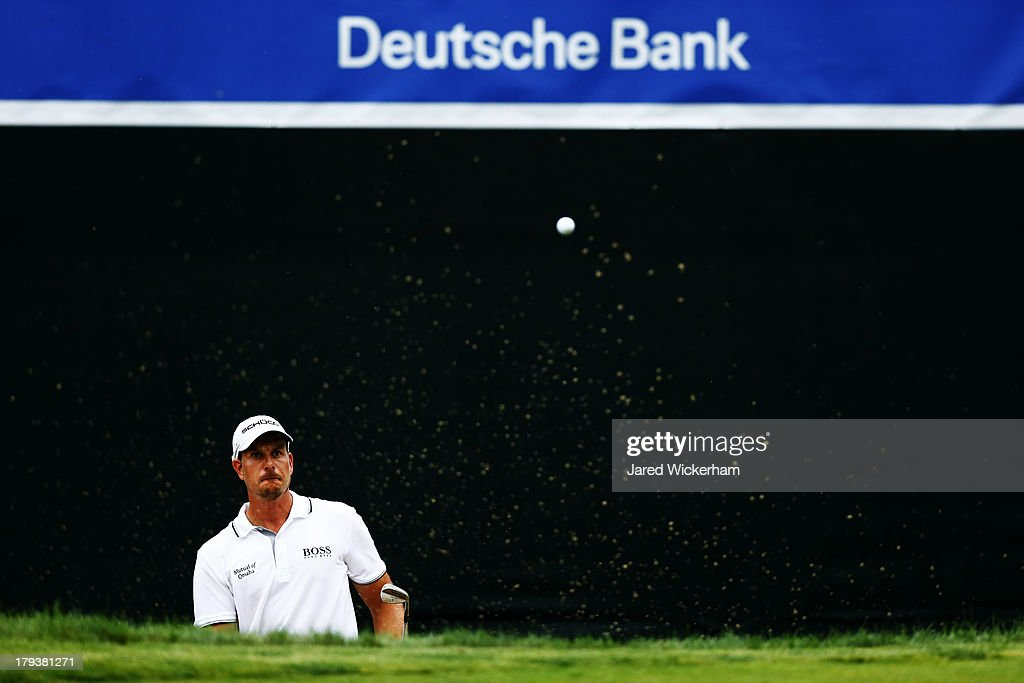 Henrik Stenson of Sweden plays a shot from a bunker into the hole on the 17th green for birdie during the final round of the Deutsche Bank...
