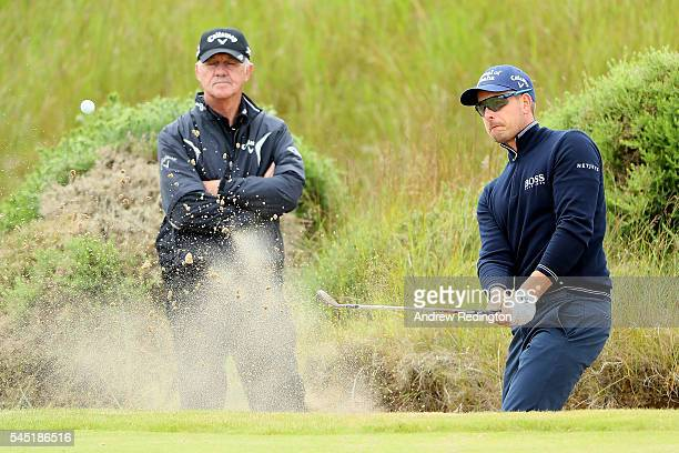 Henrik Stenson of Sweden practices his bunker play with Coach Pete Cowen during a proam round ahead of the AAM Scottish Open at Castle Stuart Golf...