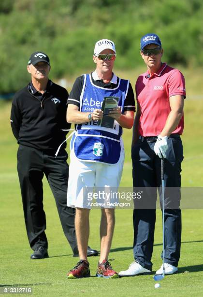 Henrik Stenson of Sweden speaks with Gareth Lord his caddie and Pete Cowen his coach during a ProAm prior to the AAM Scottish Open at Dundonald Links...