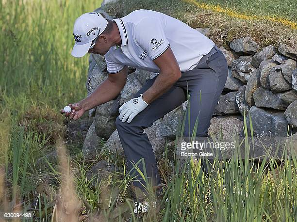 Henrik Stenson picks up his ball after he hit his tee shot out of bounds losing a stroke on the 16th hole during the finalround action of the...
